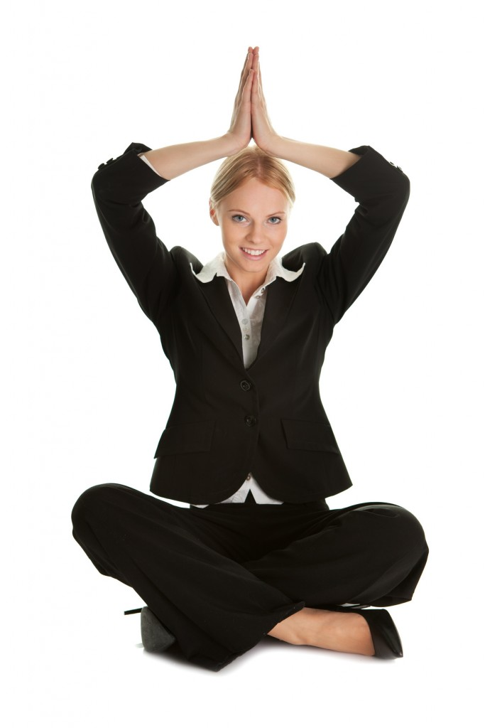 Businesswoman sitting in lotus flower position of yoga. Isolated on white